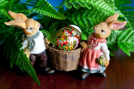 ortodox: Two rabbits carrying Easter egg on green background Stock Photo