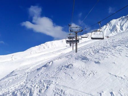 Chairlift cable car and ski slopes in the mountains photo