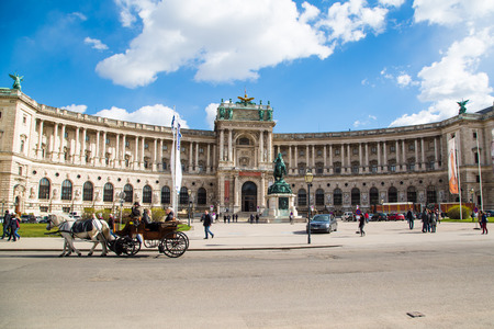 hackney carriage: Vienna, Austria - April 3, 2015: Hofburg palace and square view, people walking and fiaker with white horses  in Vienna, Austria