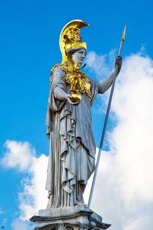 diosa griega: Estatua y fuente de Palas Atenea Brunnen, diosa griega de la sabidur�a, en el casco de oro en frente del edificio del Parlamento en Viena, Austria contra el cielo nublado azul Foto de archivo