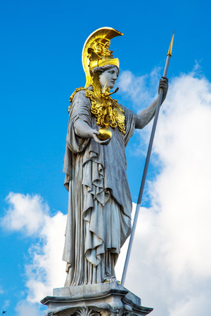 pallas: Statue and fountain of Pallas Athena Brunnen, greek goddess of wisdom, in golden helmet in front of Parliament building in Vienna, Austria against the blue cloudy sky