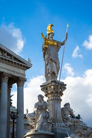 diosa griega: Edificio del Parlamento en Viena, Austria. Estatua y fuente de Palas Atenea Brunnen - diosa griega de la sabiduría - en frente de ella contra el cielo nublado azul Foto de archivo
