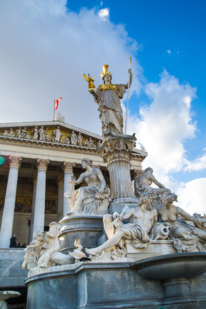 diosa griega: Edificio del Parlamento en Viena, Austria. Estatua y fuente de Palas Atenea Brunnen - diosa griega de la sabidur�a - en frente de ella contra el cielo nublado azul Foto de archivo