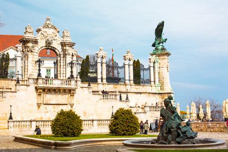 buda: Budapest, Hungary - March 29, 2015: Buda Castle Palace entrance gate, Buda Castle Palace entrance gate, Turul eagle  statue and tourists walking around Editorial