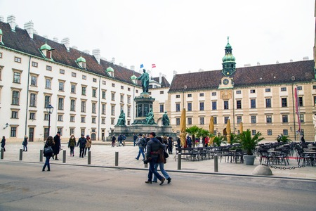 hofburg: Vienna, Austria - April, 2, 2015: Tourists near Hofburg, Innerer Burghof , Monument with Emperor Franz I posing as Caesar Augustus by the Italian sculptor Pompeo Marchesi