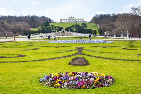 the gloriette: Vienna, Austia - April 3, 2015: View of green Flowerbed, People going towards The Neptune Fountain and Gloriette at the Schonbrunn, Vienna, Austria