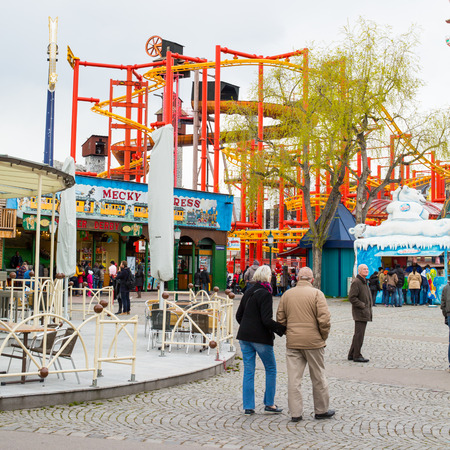 prater: Vienna, Austria - April 5, 2015: View of the various attractions situated inside of the Prater amusement park in Vienna and people walking around