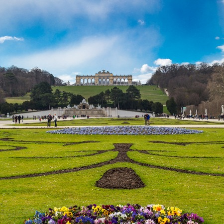 gloriette: Vienna, Austia - April 3, 2015: View of green Flowerbed, People going towards The Neptune Fountain and Gloriette at the Schonbrunn, Vienna, Austria