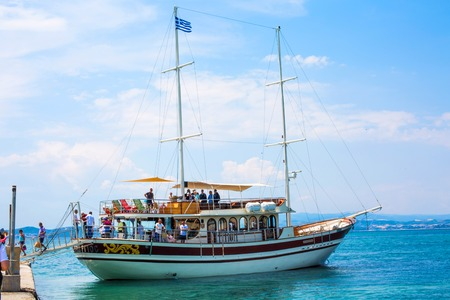 descend: Ouranoupolis , Greece - June, 1, 2015:  Tourists descend from ship under Greek flag in Ouranoupolis port, harbor in Athos, Halkidiki, Greece, Aegean sea after the sea trip to the monasteries