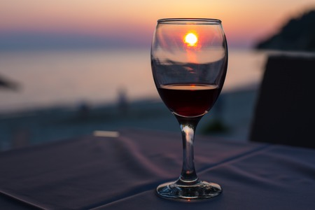 Sunset on beach reflected in glass of red wine summertime vacation concept. Place for text Standard-Bild
