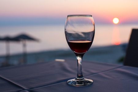 glass with red wine and sunset on beach  at the background. Summertime vacation concept. Place for text