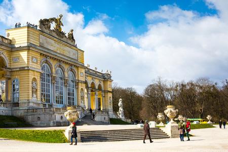 gloriette: Vienna, Austia - April 3, 2015: The Gloriette in the Schonbrunn Palace Garden, Vienna, Austria against the cloudy blue sky. Tourists walking around.