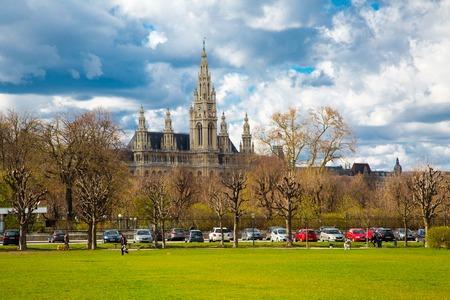 rathaus: Vienna, Austria - April 3, 2015: Part of the park near Hofburg, Vienna Town Hall,  Wiener Rathaus, Austria against the cloudy sunny sky Editorial