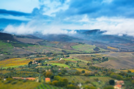 tilt and shift: Beautiful colorful Tuscany panoramic landscape with fields, trees and houses,  Italy and blue sky. tilt shift effect