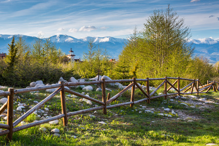 fence: Landscape with the wooden fence, Vibrant spring trees, part of the wooden tower of chalet and snowy peaks of mountains in Bansko, Bulgaria