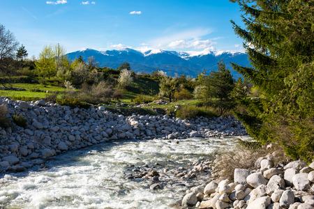 sprung: Spring has sprung. The river, vibrant green trees. Snowy mountains far away