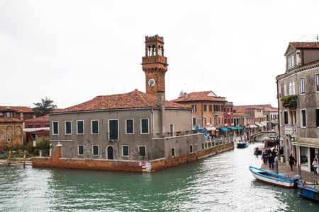 canal street: Murano island, Venice, Italy - November 11, 2014: Canal and tower view  in Murano island,boats  and people at the street Editorial