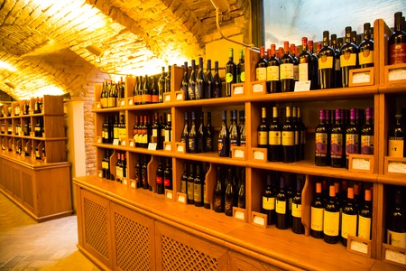 Dozza,  Italy - November, 13,2014: Wine bottles on wooden shelfs in vintage authentic Italian wine store in the cellar interior 新聞圖片