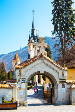 saint nicholas: Brasov, Romania - March 24, 2015: The entrance gate and Saint Nicholas Church in Brasov, Transilvania, Romania and people going inside Editorial