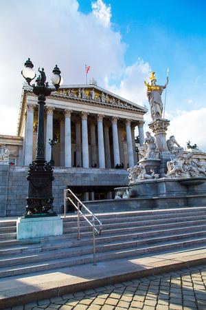 diosa griega: Viena, Austria - 03 de abril 2015: Estatua y fuente de Palas Atenea Brunnen, diosa griega de la sabidur�a, en el casco de oro en frente del edificio del Parlamento en Viena, Austria contra el fondo del cielo nublado azul. Los turistas cerca de ella Editorial