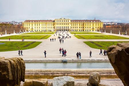 neptuno: Viena, Austria - 3 abril 2015: Palacio de Schonbrunn vista desde la fuente de Neptuno y turistas caminando.