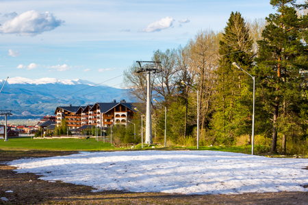 sprung: Spring has sprung. Melting last snow and vibrant green trees at the pathway. Wooden Chalet far away. Bansko, Bulgaria