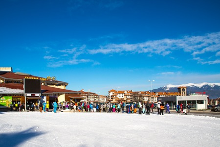 station ski: Bansko, Bulgaria - February 19, 2015: Bansko ski station, cable car lift and people waiting in line near it in Bansko, Bulgaria. Snow mountain peaks and blue sky at the background
