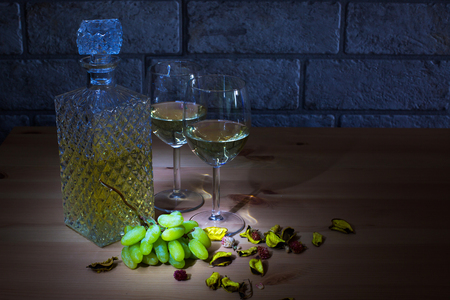 winy: Lightened crystal carafe of white wine, two glass, grapes on wooden table and gray bricks background with place for text