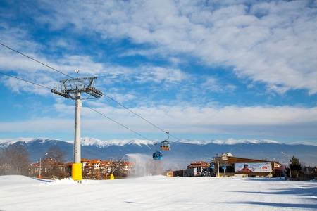station ski: Bansko, Bulgaria - February 19, 2015: Bansko ski station, cable car lift in Bansko, Bulgaria and snow peaks of the mountains