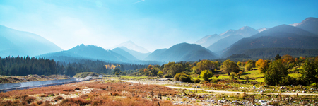 fall landscape: Vibrant autumn panorama background of Pirin, Bulgaria with colorful green, red and yellow trees and mountains peaks