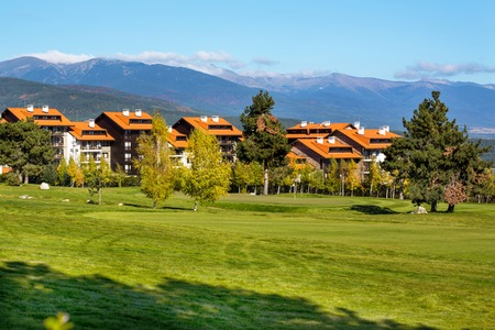 chalets: Panorama of Beautiful autumn Landscape view of green, grass, colorful trees, wooden chalets with red roofs and mountains background