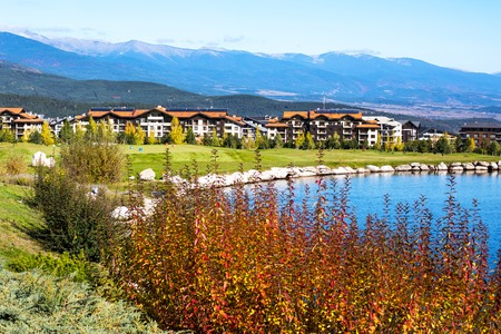 chalets: Beautiful autumn Landscape view of the lake, colorful trees, wooden chalets with red roofs and mountains background