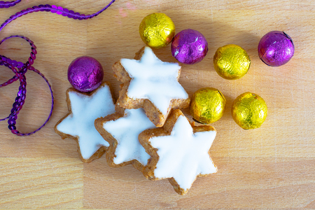 star of life: Still life with holiday decoration, star shape Christmas cookies, purple and yellow golden sweet candy balls close up