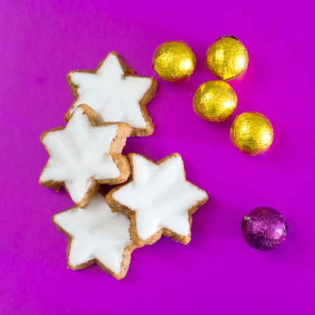 star of life: Still life with star shape Christmas cookies, purple and yellow golden sweet candy balls close up