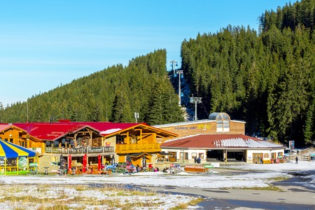 car lift: Bansko, Bulgaria - December, 6, 2015: Bunderishka polyana, ski station, cable car lift, Bansko, Bulgaria,  blue cabins and mountain with pine trees, people Editorial