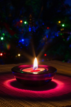 tea candle: Christmas holiday background with purple tea candle and colorful lights of Christmas tree with copyspace