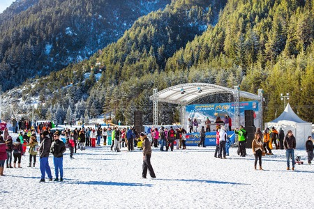 ski walking: Bansko, Bulgaria - December, 12, 2015: Ski resort Bansko, Bulgaria, mountain with pine trees, people walking
