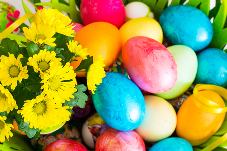 orthodox easter: Vibrant color holiday background. Still life with nice spring yellow flowers and colorful Easter eggs