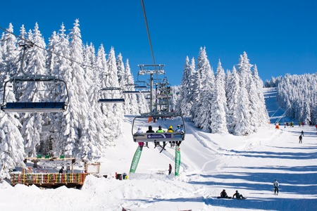 ski walking: Kopaonik, Serbia - January 19, 2016: Ski resort Kopaonik, Serbia, ski slope, people on the ski lift, skiers on the piste among white snow pine trees forest