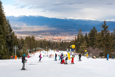 ski lift: Bansko, Bulgaria - February 11, 2016:  Skiers on the slope , ski lift, mountains view and Bansko town panorama