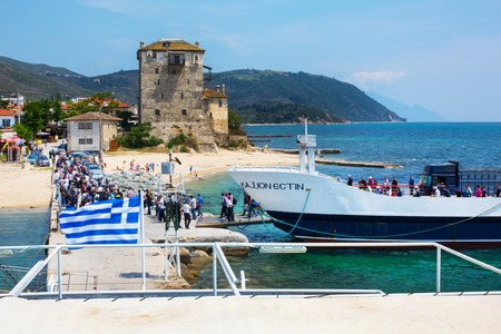 descend: Ouranoupolis , Greece - June, 1, 2015:  Tourists descend from ship under Greek flag in Ouranoupolis port, harbor in Athos, Halkidiki, Greece, Aegean sea. Ouranoupolis tower view Editorial