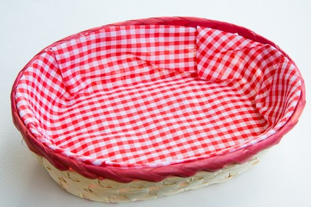 breadbasket: Wicker basket for bread  with red and white plaid cloth on white background