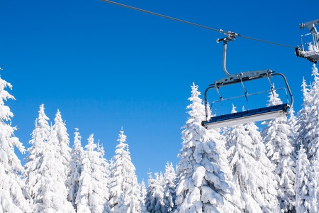 chair on the lift: Ski resort image with empty chair lift, blue sky and white snowy pine trees at winter sunny day Stock Photo