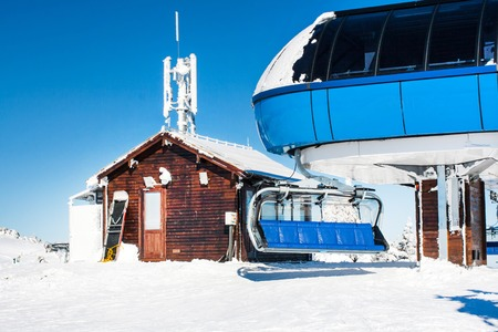 chair on the lift: Ski resort image with  empty chair lift at high station, winter sunny day Stock Photo