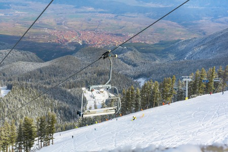 chair on the lift: Bansko, Bulgaria - March 4, 2016: Ski resort Bansko, Bulgaria aerial view, chair lift, people skiing on slopes, town panorama