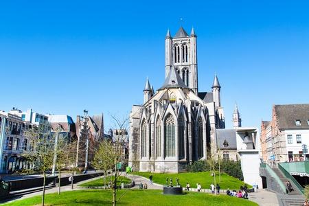st nicholas: Ghent, Belgium - April 12, 2016: Vibrant color view of St Nicholas Church in Ghent,  Belgium and people in the park near it Editorial