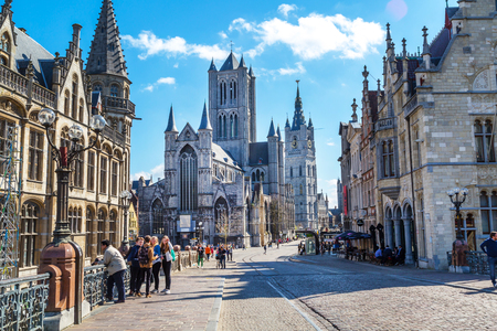 stoned: Ghent, Belgium - April 12, 2016: Vibrant color street view of Ghent, Belgium with St Nicholas Church, beautiful houses and people near it Editorial