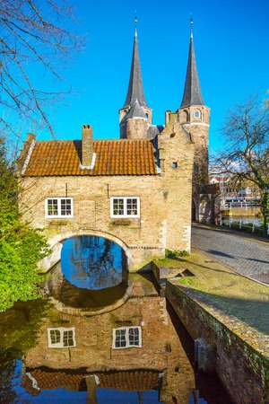 canal house: Colorful Oostpoort or Eastern Gate domes, canal and house reflection, Delft, Netherlands, Holland against blue sky