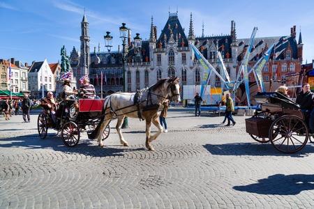 hackney carriage: Bruges, Belgium - April 10, 2016:  Fiaker with tourists in Market place or Grote Markt square,  popular belgian destination Brugge, Belgium Editorial