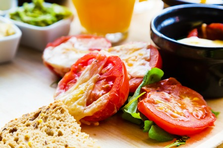 colorful still life: Healthy food background with tomato backed with cheese, green leafs, healthy colorful organic still life